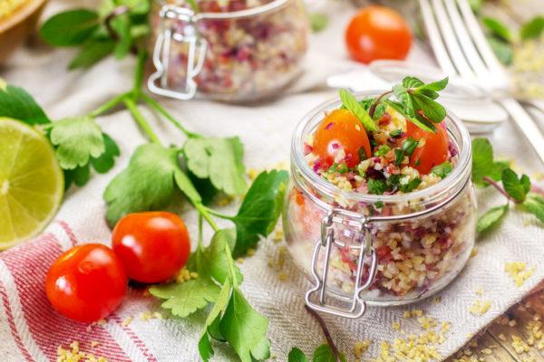 Vasetto in vetrno con insalata di bulgur, pomodorini e prezzemolo su tovaglia