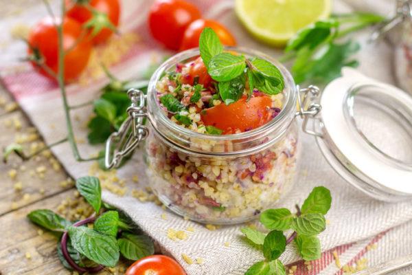 Vasetto in vetro con insalata di bulgur, pomodorini e foglie di monta, condita con gli scarti del succo di mela, carota, cavolo rosso e lime