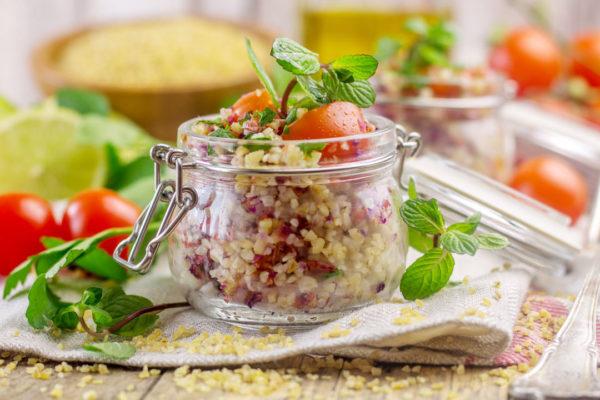 Vasetto su tavolo con insalata di bulgur e foglie di menta